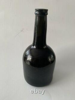 An antique black glass bottle from the end of the 18th. Century, onion bottle